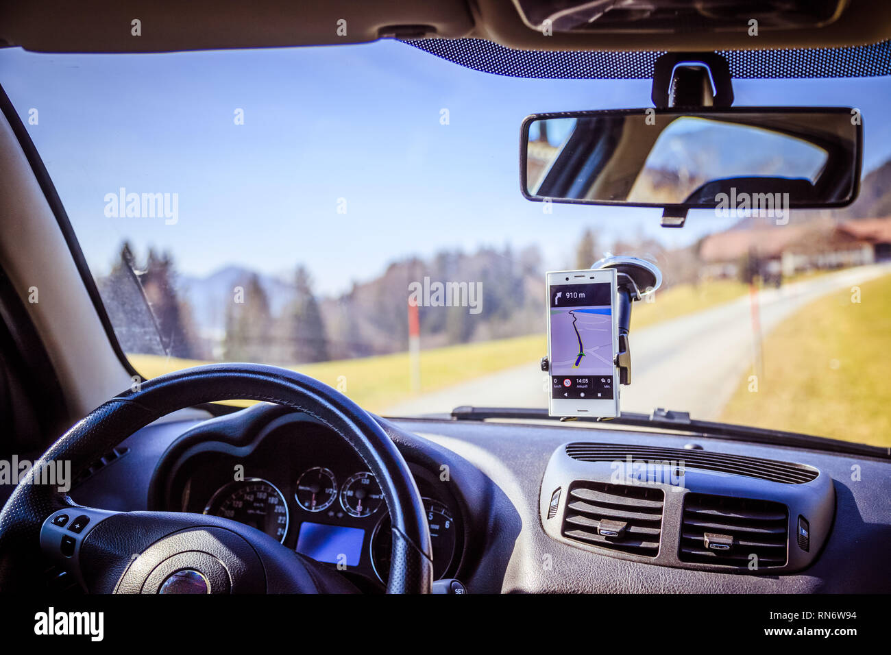 Interior of a modern car on a sunny day. Smartphone on mobile mount, used as navigation device - Stock Image