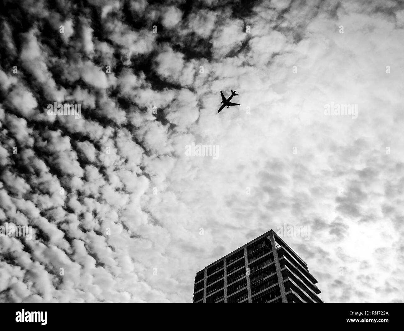 Airplane flying in the sky above the skyscraper. Tel-Aviv, Israel - Stock Image
