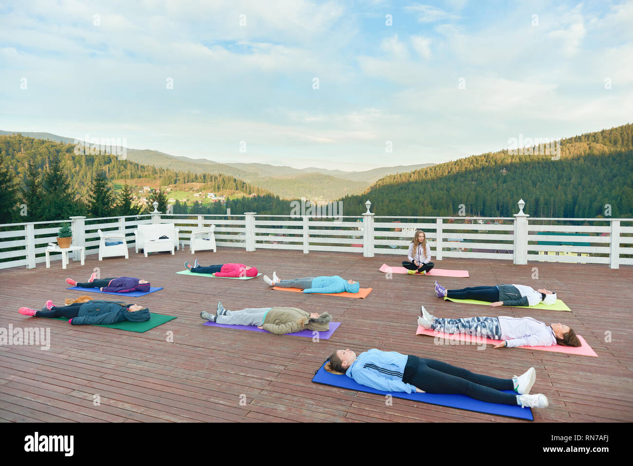 Yoga group practising relaxation on fresh air in mountains. People wearing in sportswear lying on special yoga mats, relaxing and enjoying nature. - Stock Image