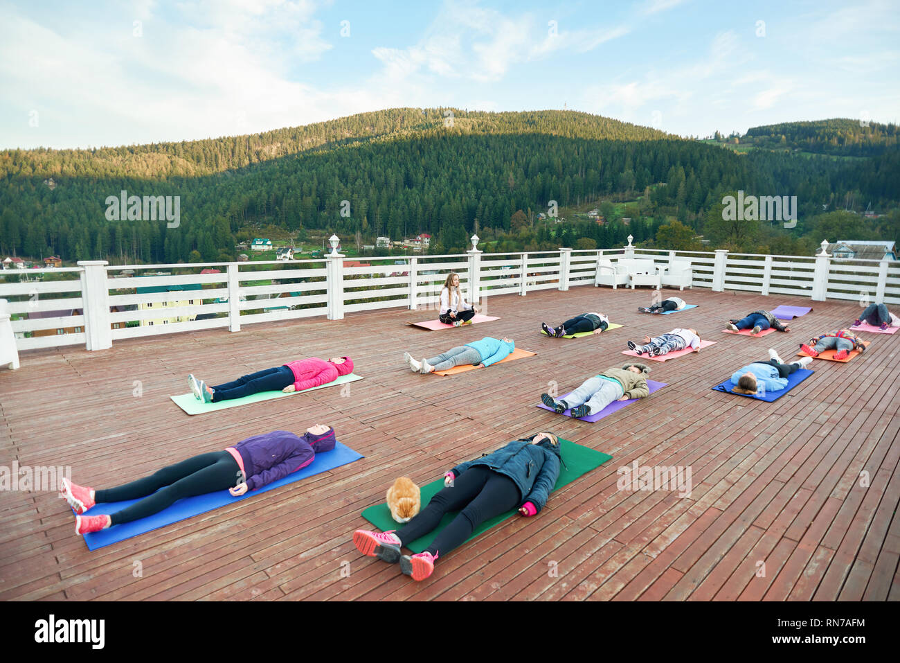 People practicing yoga with yoga teacher in mountains on fresh air. Coach sitting and observing. Group lying on yoga mats, looking up and relaxing outside. - Stock Image