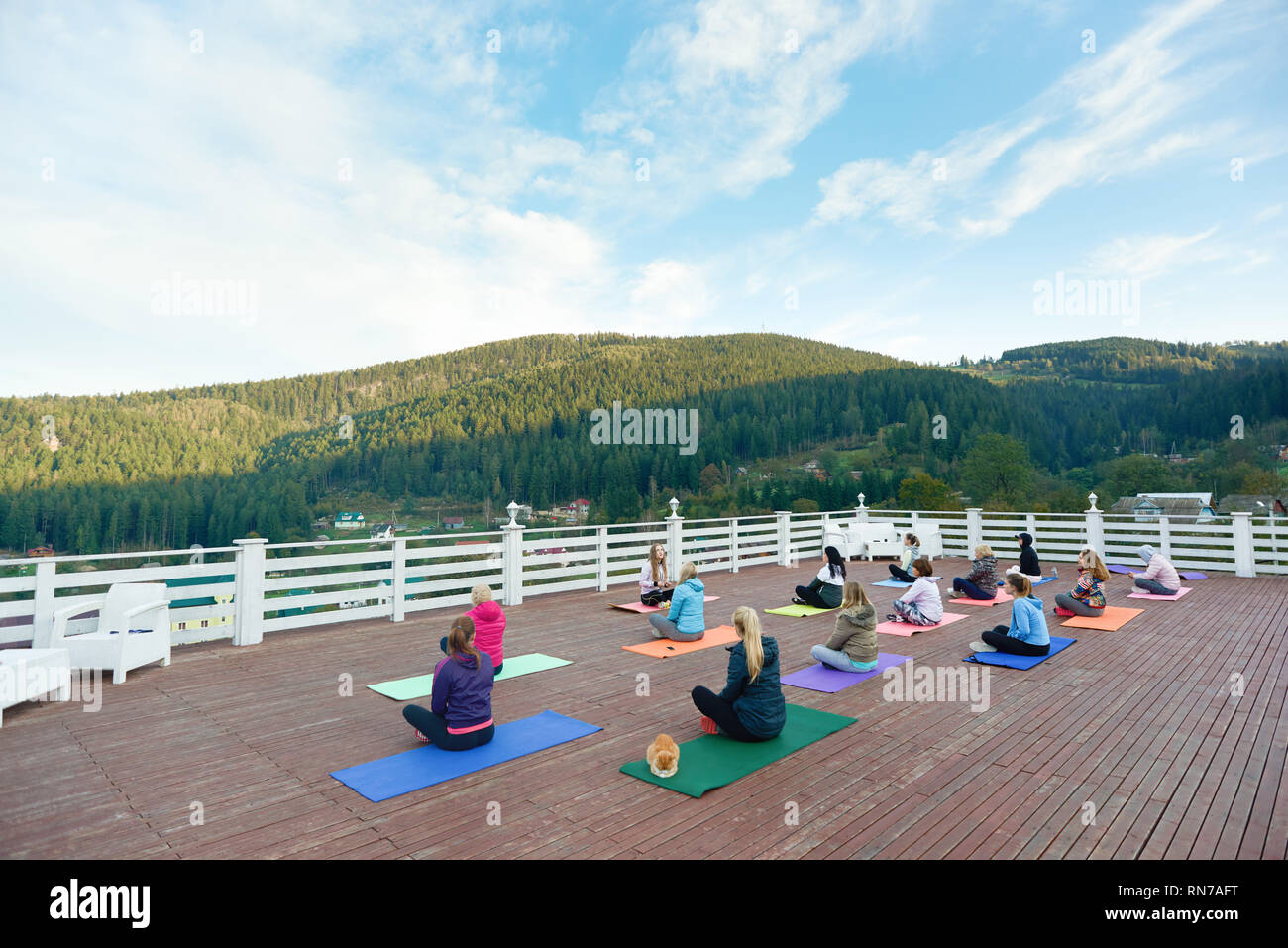 Group of people doing yoga together with coach on fresh air. People sitting in lotus pose observing amazing view of mountains. Women practicing on yoga mats, wearing in sportswear. - Stock Image