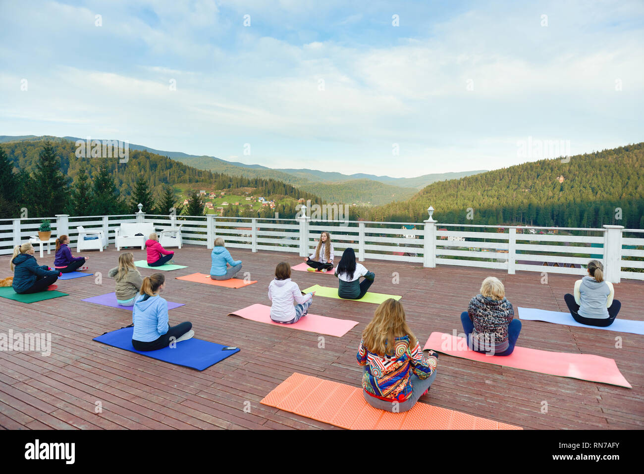 Woman practicing yoga with coach, sitting in lotus pose on yoga mats. Instructor teaching yoga in mountains on fresh air. Yoga group relaxing and enjoying amazing view. - Stock Image