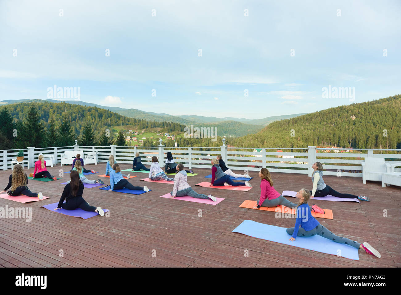Yoga group doing stretching and yoga on fitness class with coach. Flexible women wearing in sportswear practicing on yoga mats. People exercising on fresh air in mountains. - Stock Image