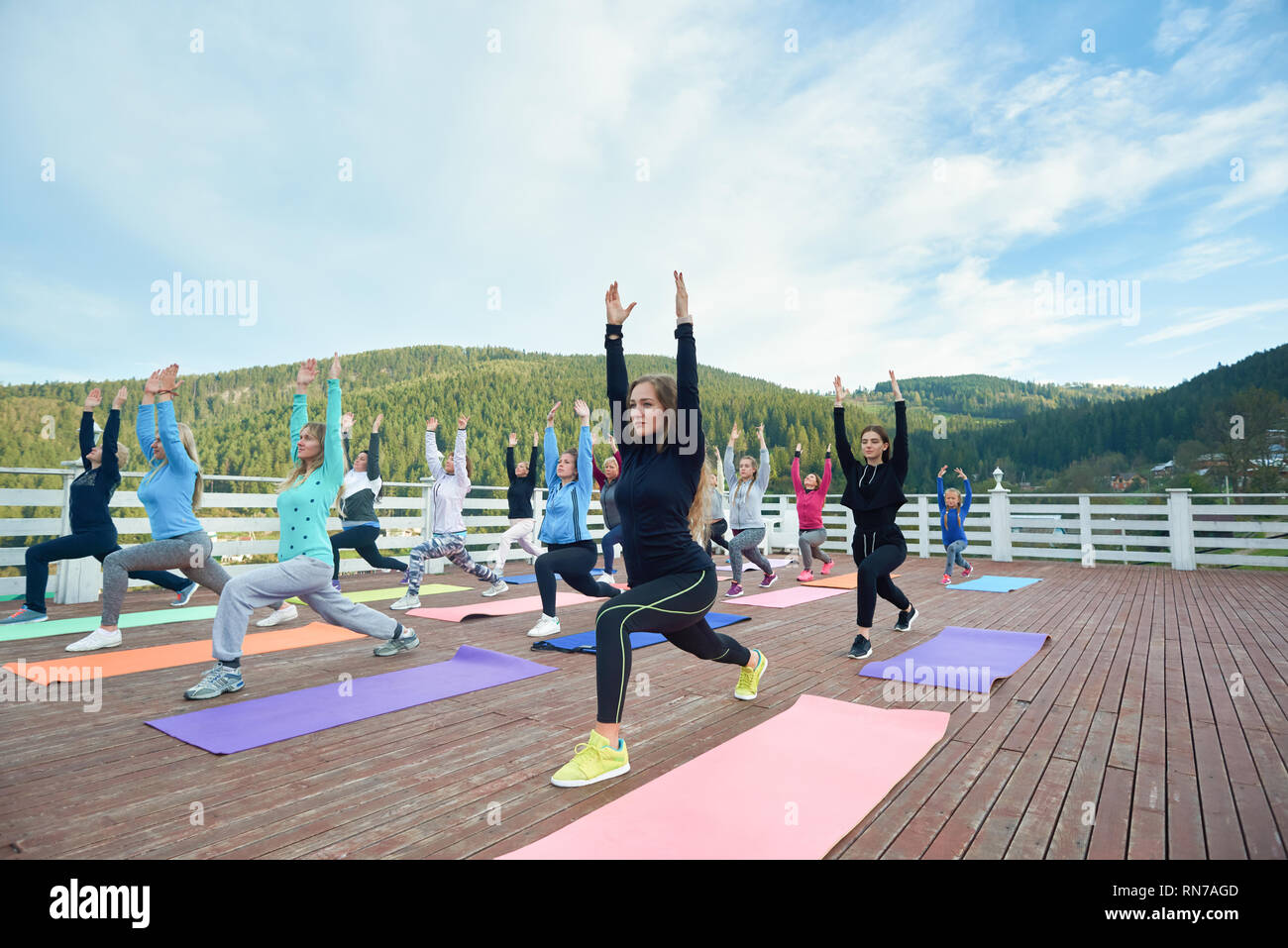 Women practicing low lung pose on yoga class. Group doing yoga exercises with coach on fresh air in mountains. People in sportswear stretching on special yoga mats. - Stock Image