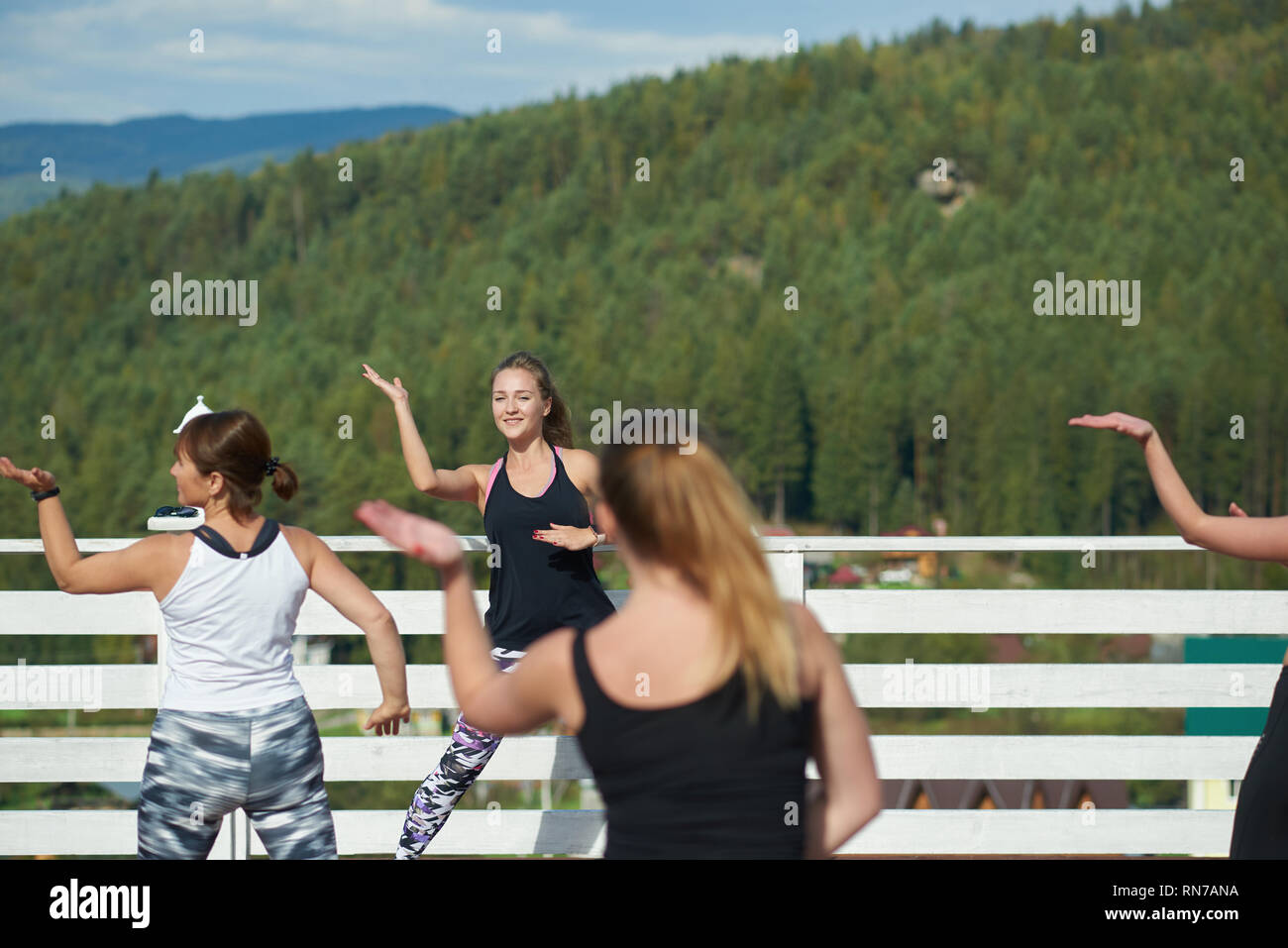 Professional fitness coach training sports, showing moves to women. Group repeating moves, doing exercises and practicing fitness on fresh air. Women wearing in sportswear. - Stock Image