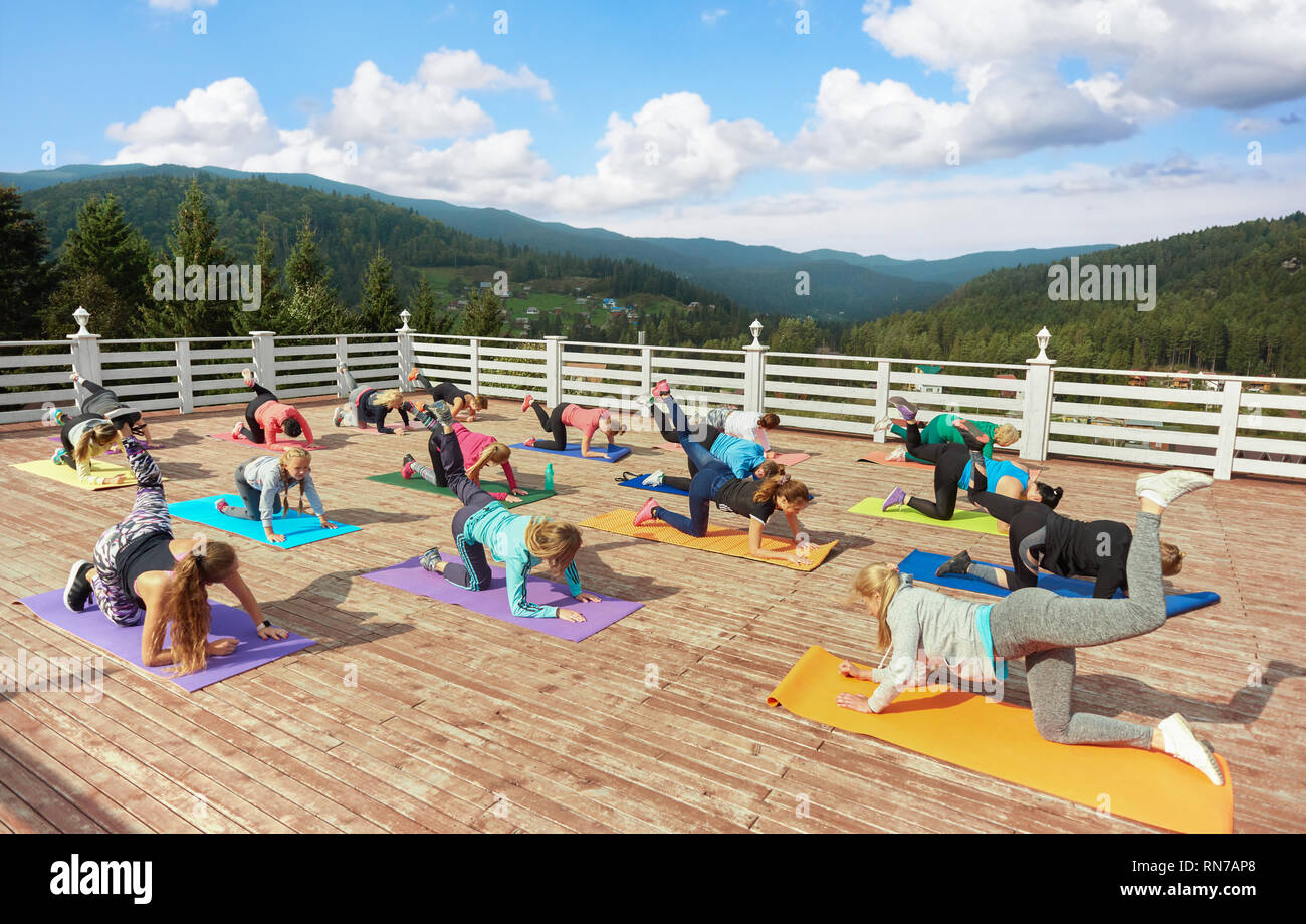 Group of women training on fitness class with coach. Sportive and healthy woman and girls standing in table top pose with raised leg and balancing. Women practicing on yoga mats. - Stock Image