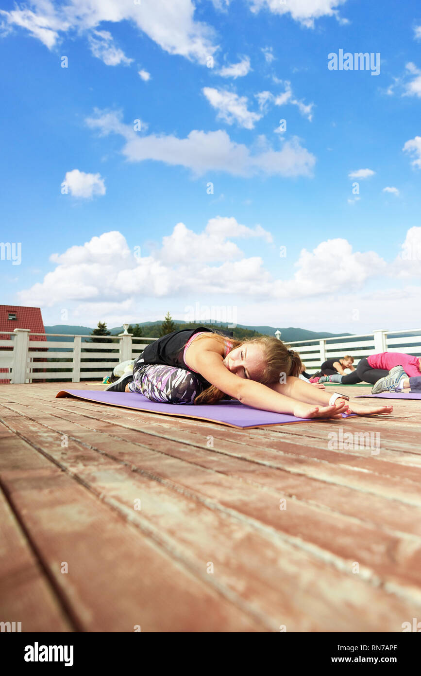 Happy woman practicing and relaxing on yoga class. Flexible woman sitting in child's pose during yoga class. Yoga coach wearing in trendy sportswear doing exercise on mat. - Stock Image