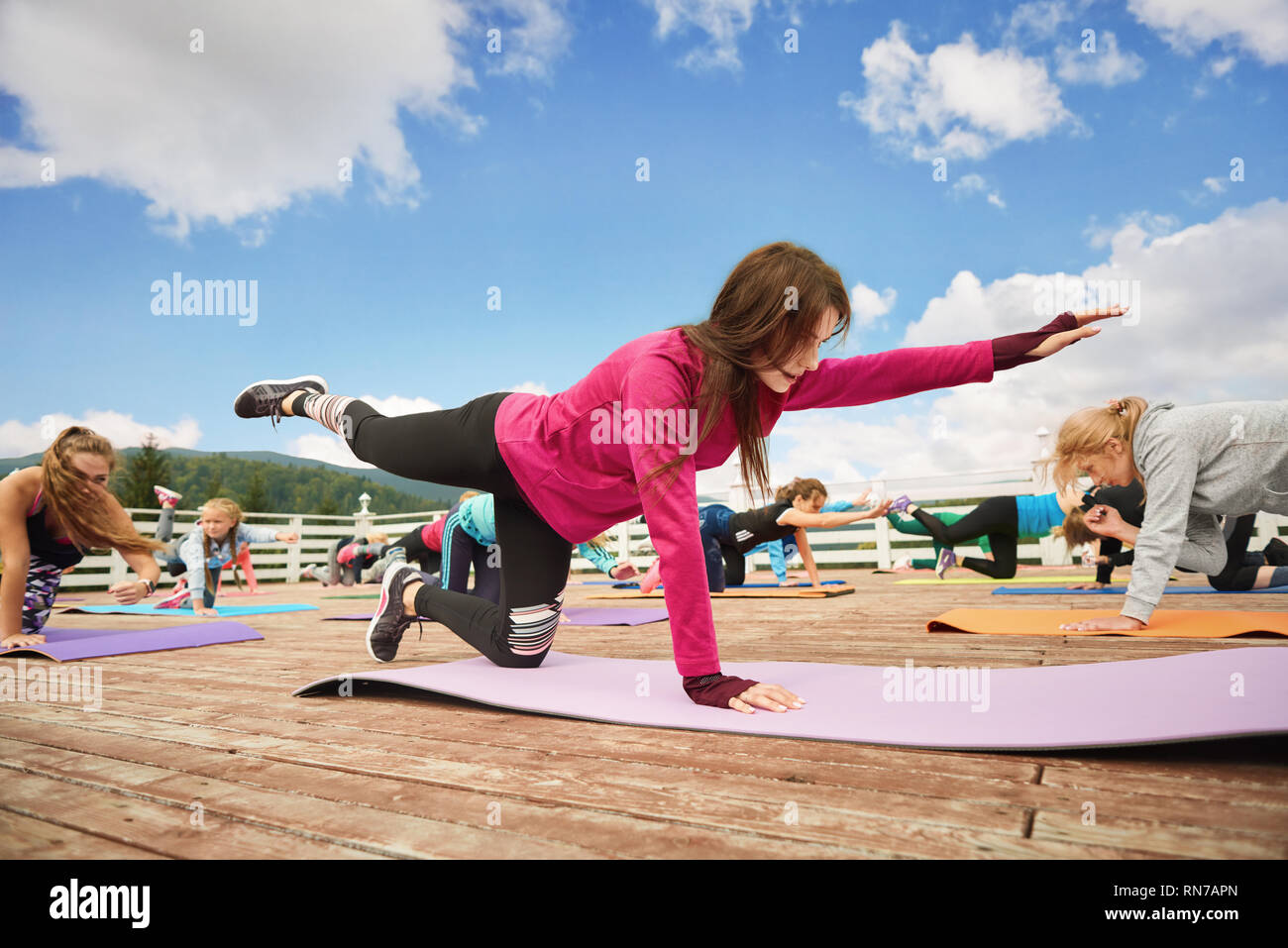 Balance exercises on yoga class. Woman standing in balancing table top pose on yoga mat. Sportive and slender coach training other women yoga, concentration and strenght. - Stock Image