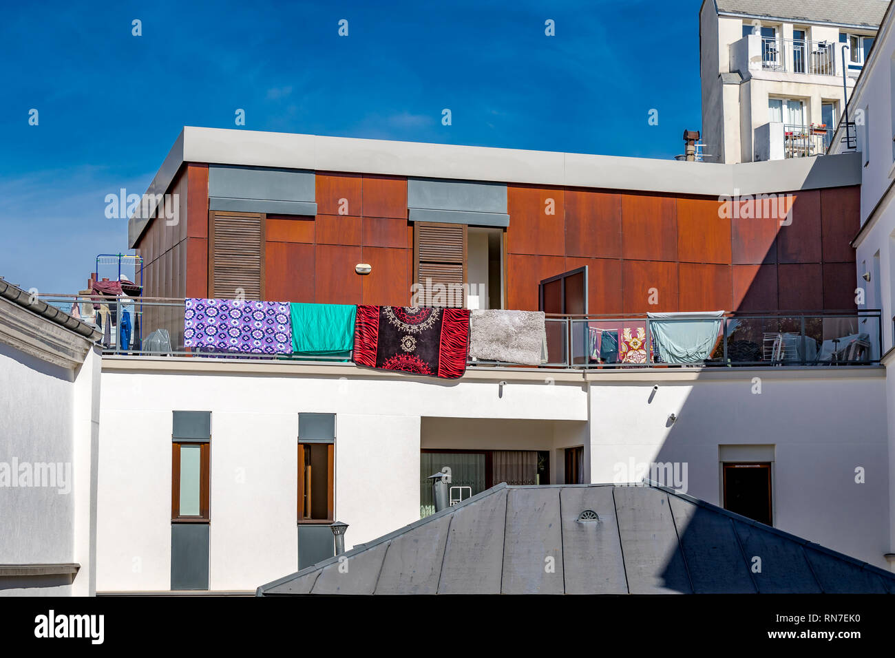 Brightly coloured rugs hanging over a balcony in the summer sunshine in Paris in front of a Paris apartment with brown wooden cladding panels ,Paris - Stock Image