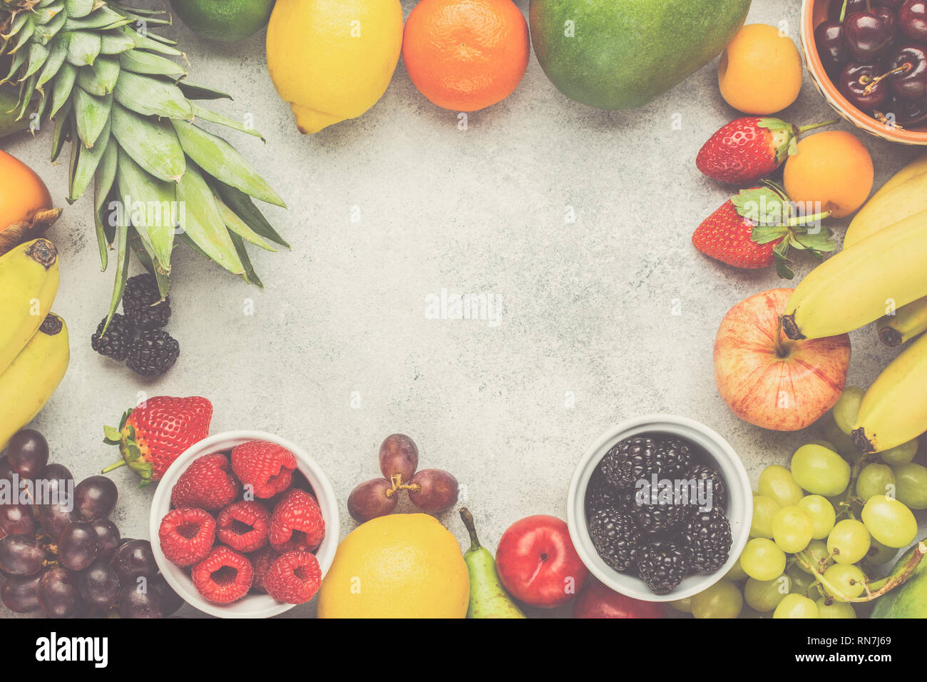 Frame made of ripe fruits, strawberries raspberries oranges plums apples kiwis grapes blueberries mango persimmon on the white table, top view, copy space, toned, selective focus - Stock Image