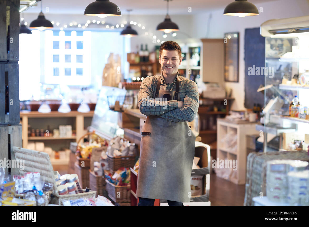 Portrait Of Smiling Male Owner Of Delicatessen Shop Wearing Apron Stock Photo