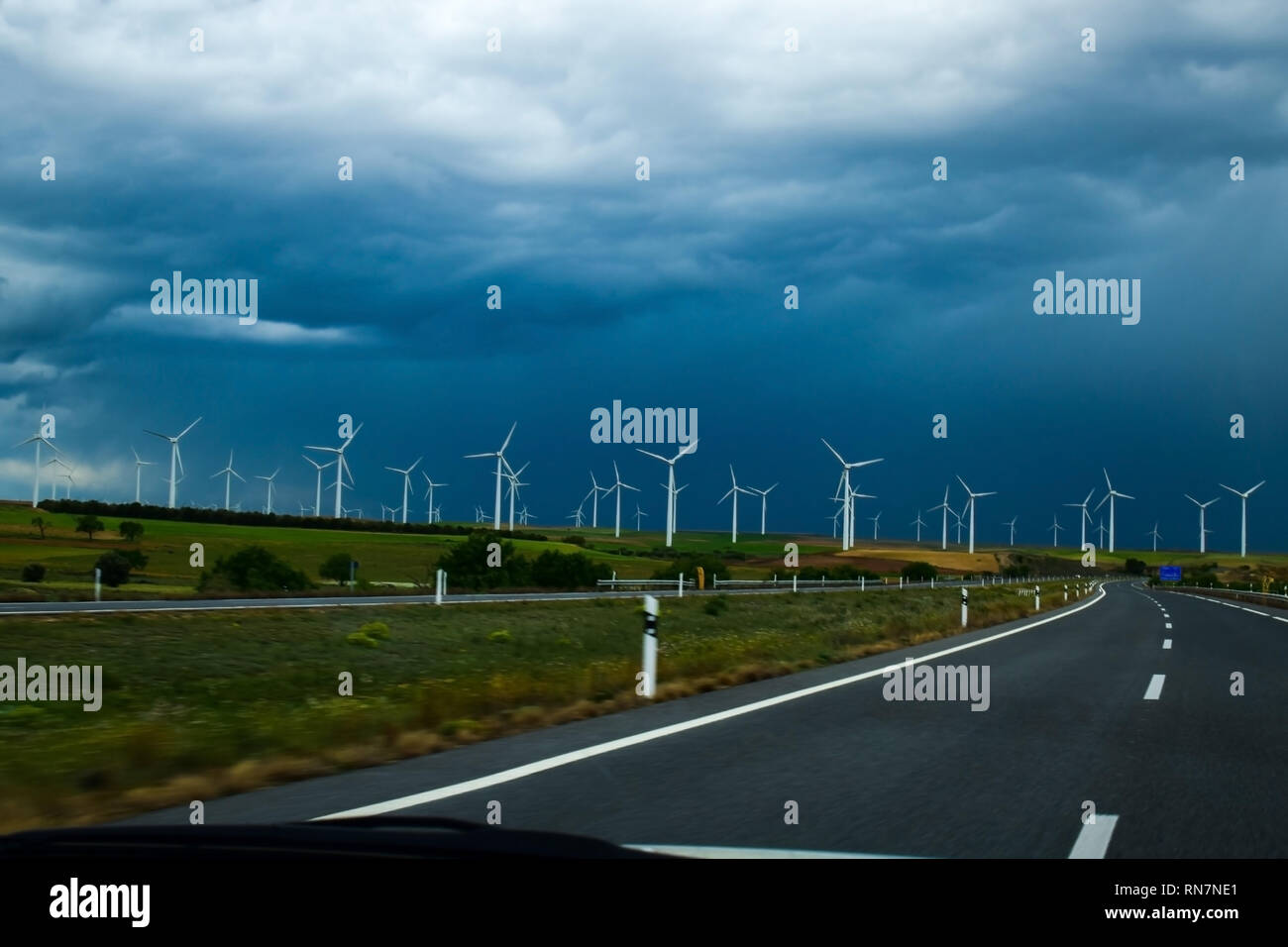 Windmill turbines power plant for electricity generation close to road. Environmentally friendly electricity production. - Stock Image