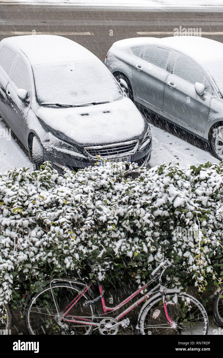 Strasbourg, Alsace, France, snowy parked cars on pavement, bicycle, - Stock Image