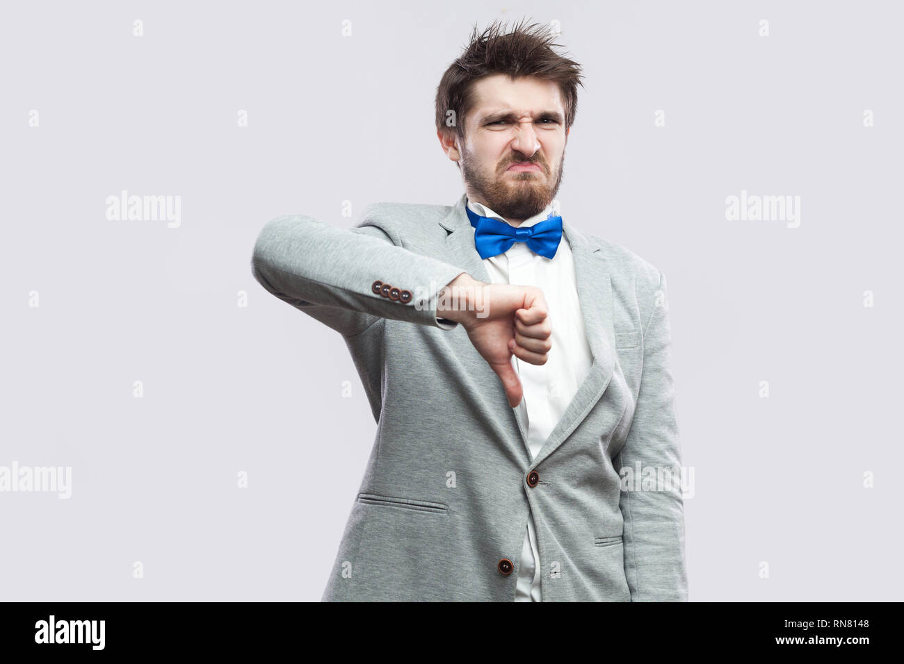 07d55d716e52 Portrait of dissatisfied handsome bearded man in casual grey suit and blue  bow tie