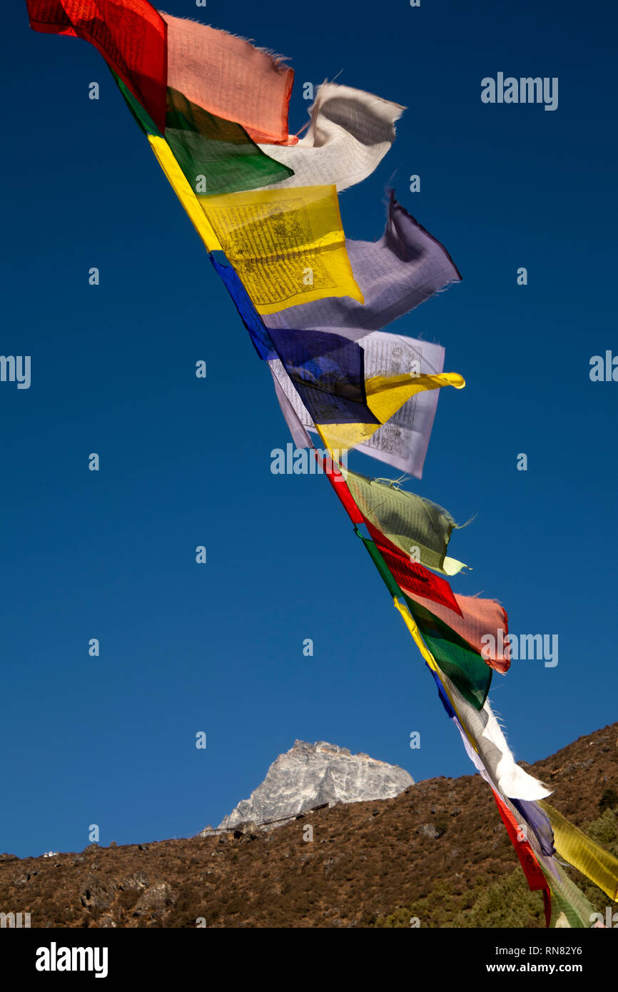 Nepal, Namche Bazaar, Busshist prayer flags flying in front of mountain peak - Stock Image