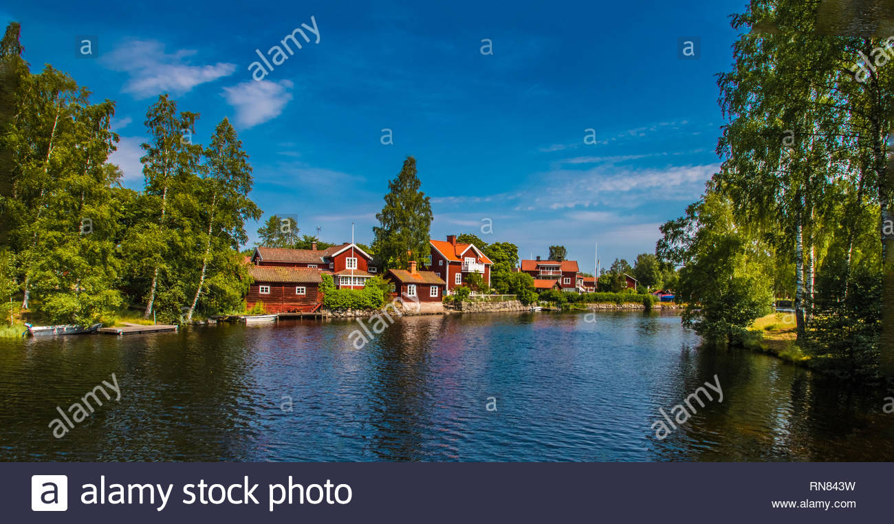 typical red swedish houses near by the pond - Stock Image