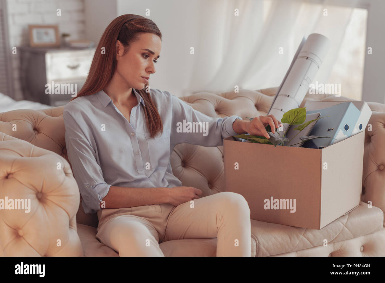 Again unemployed. Young dispirited woman sitting on sofa and being lost in thoughts while touching a box with her office property - Stock Image