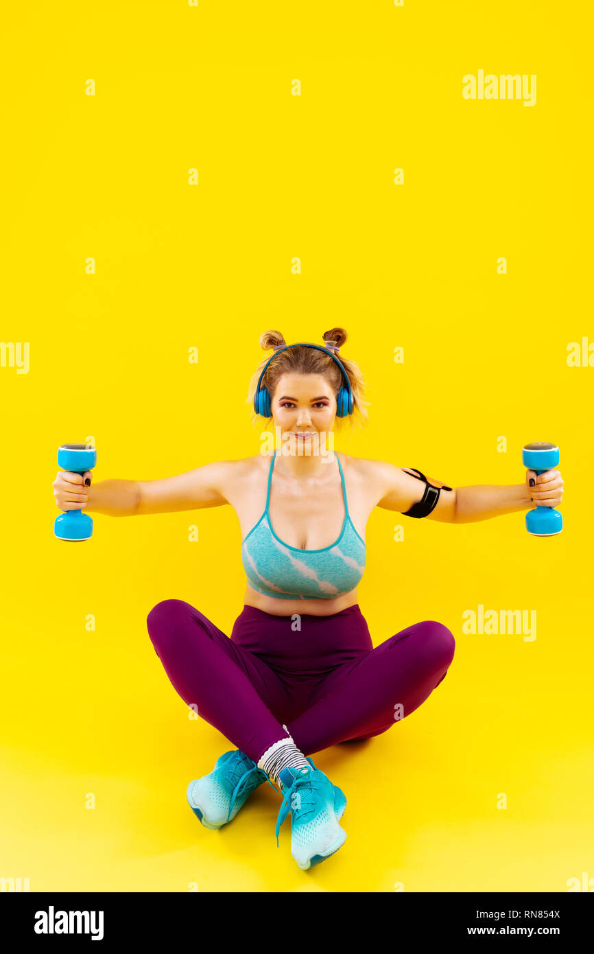 Woman wearing bright leggings and short top working out - Stock Image