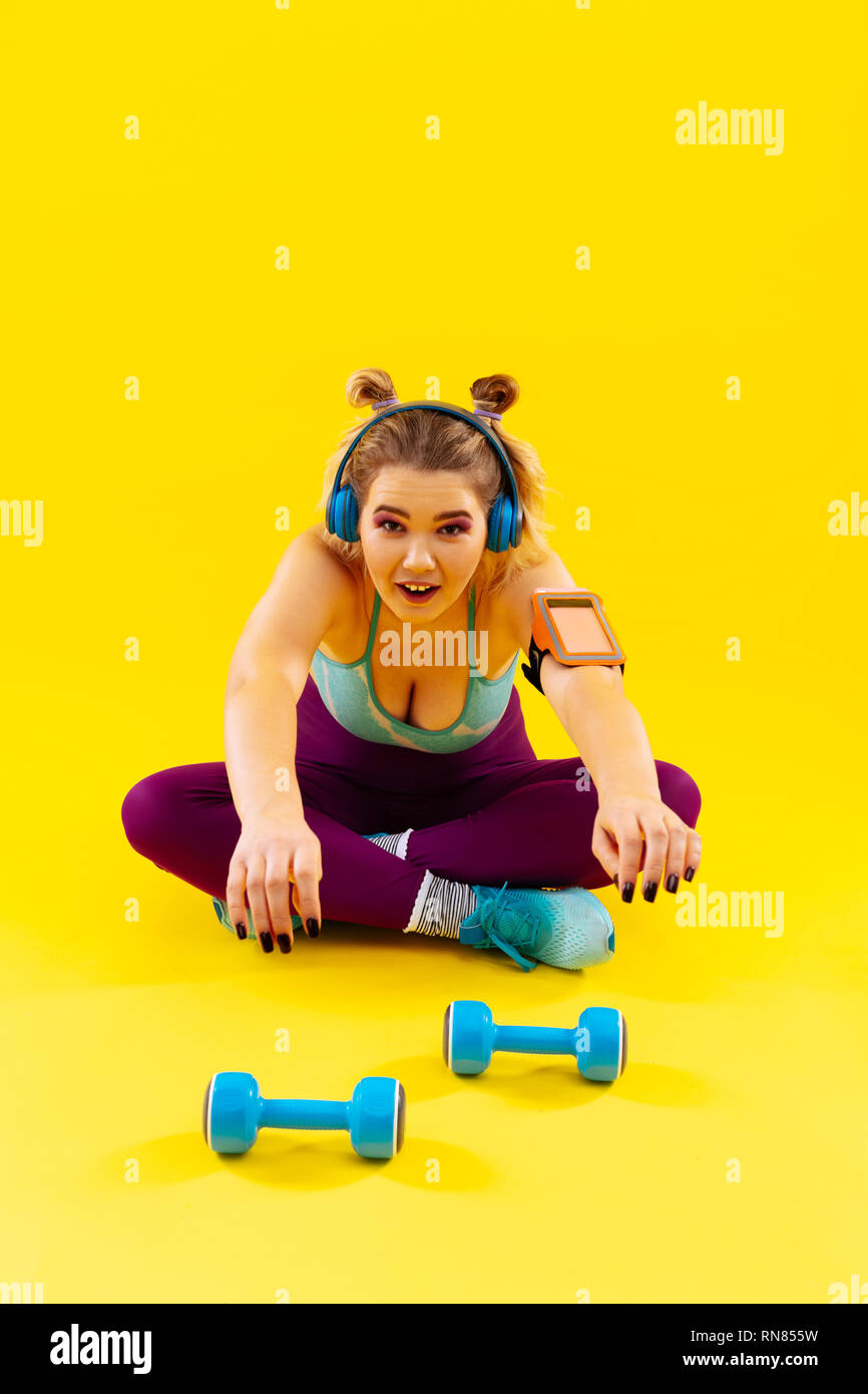 Woman loving weights feeling tired after exercising in the morning - Stock Image