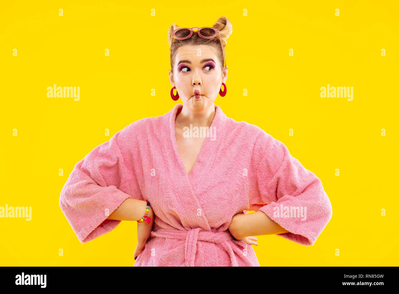 Cheerful woman with pink eye shades making funny face - Stock Image