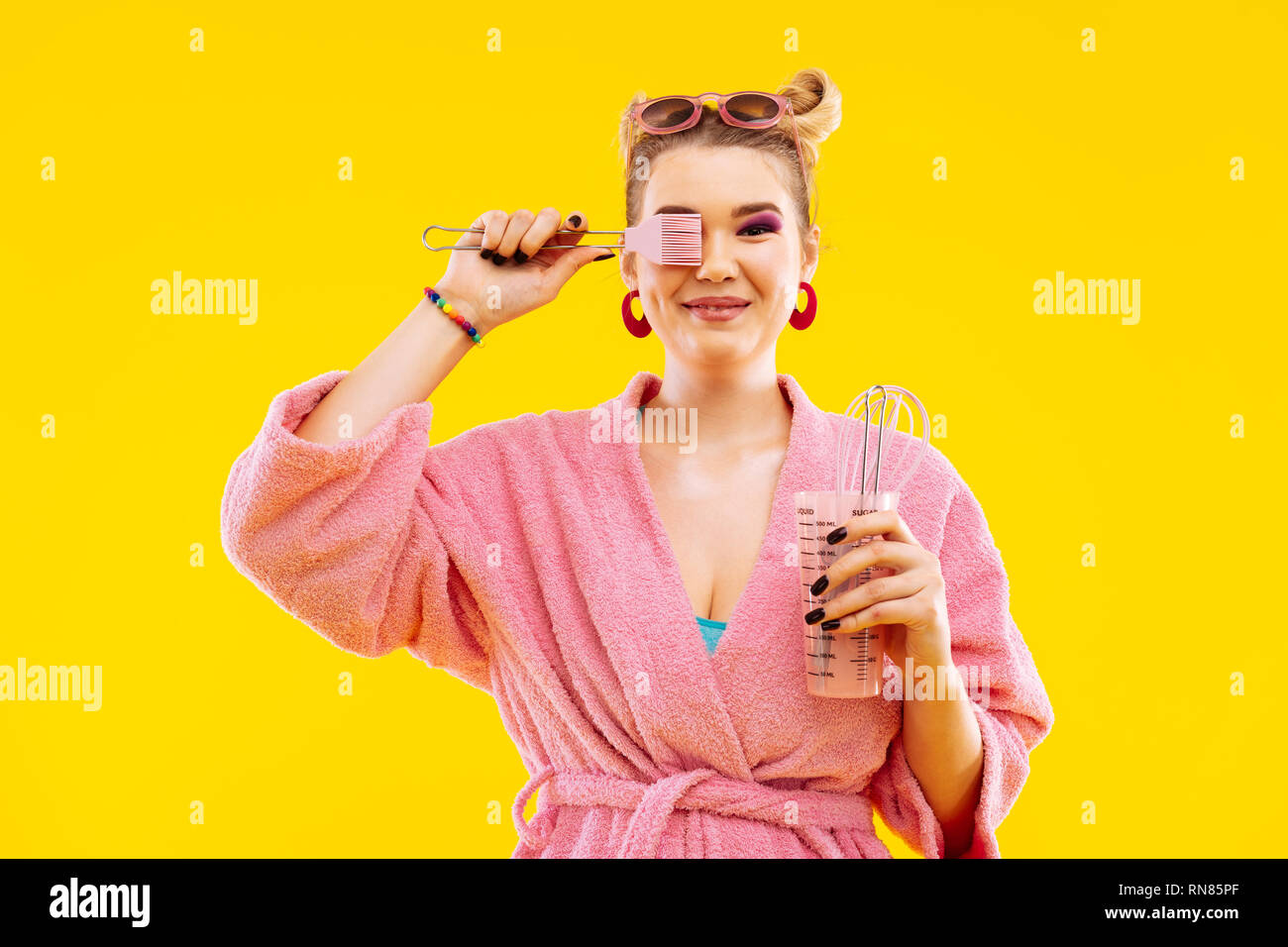 Housewife wearing bathrobe holding kitchen utensils before cooking - Stock Image
