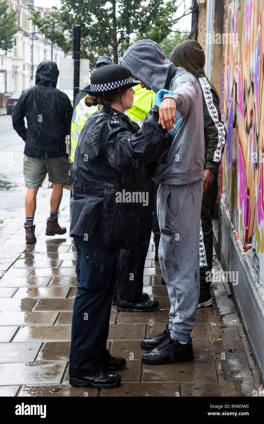 Police perform stop and search operation at Notting Hill Carnival, London, England, United Kingdom - Stock Image