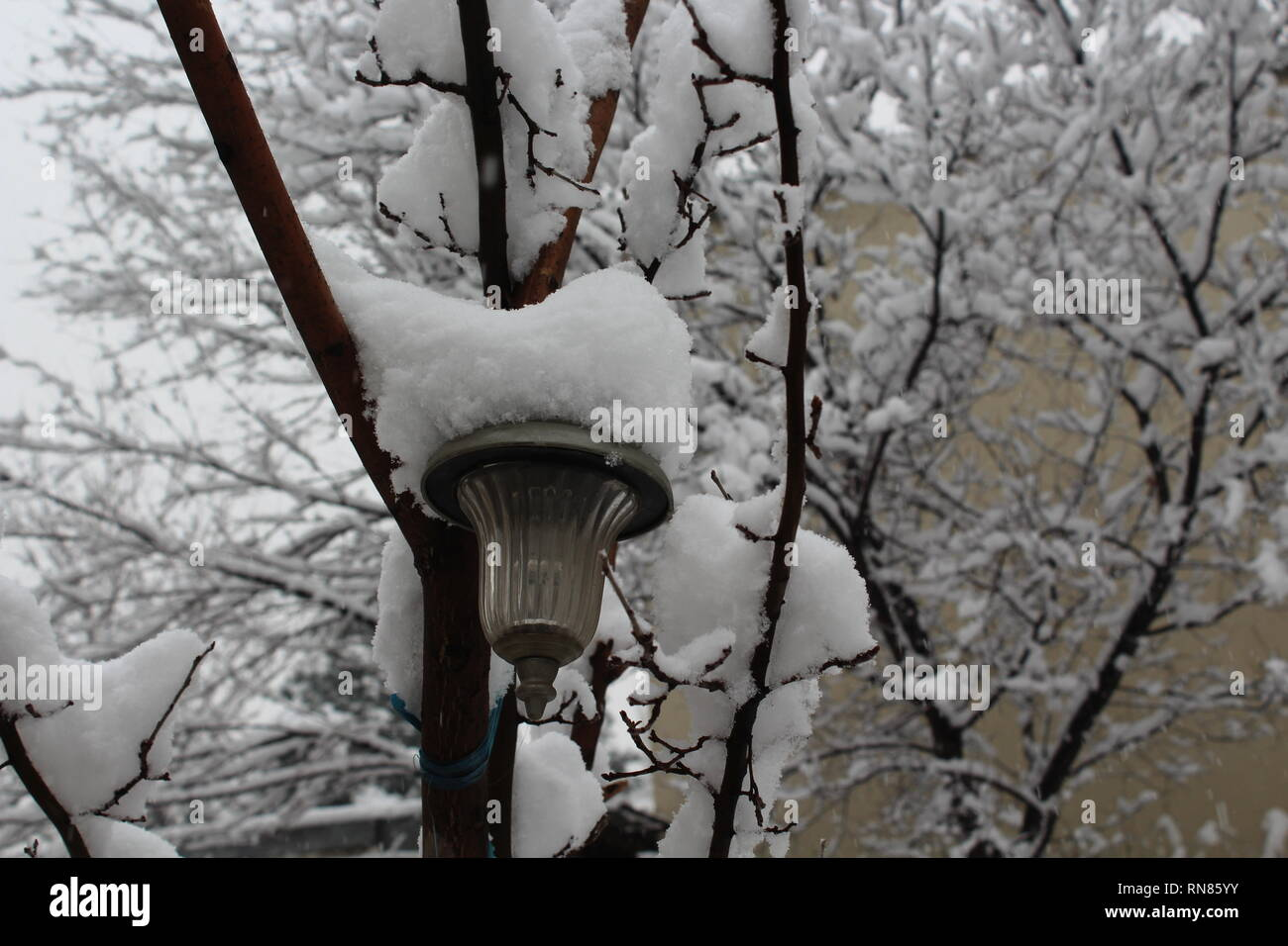 An outdoor pendant light covered with snow in Kabul, Afghanistan. - Stock Image