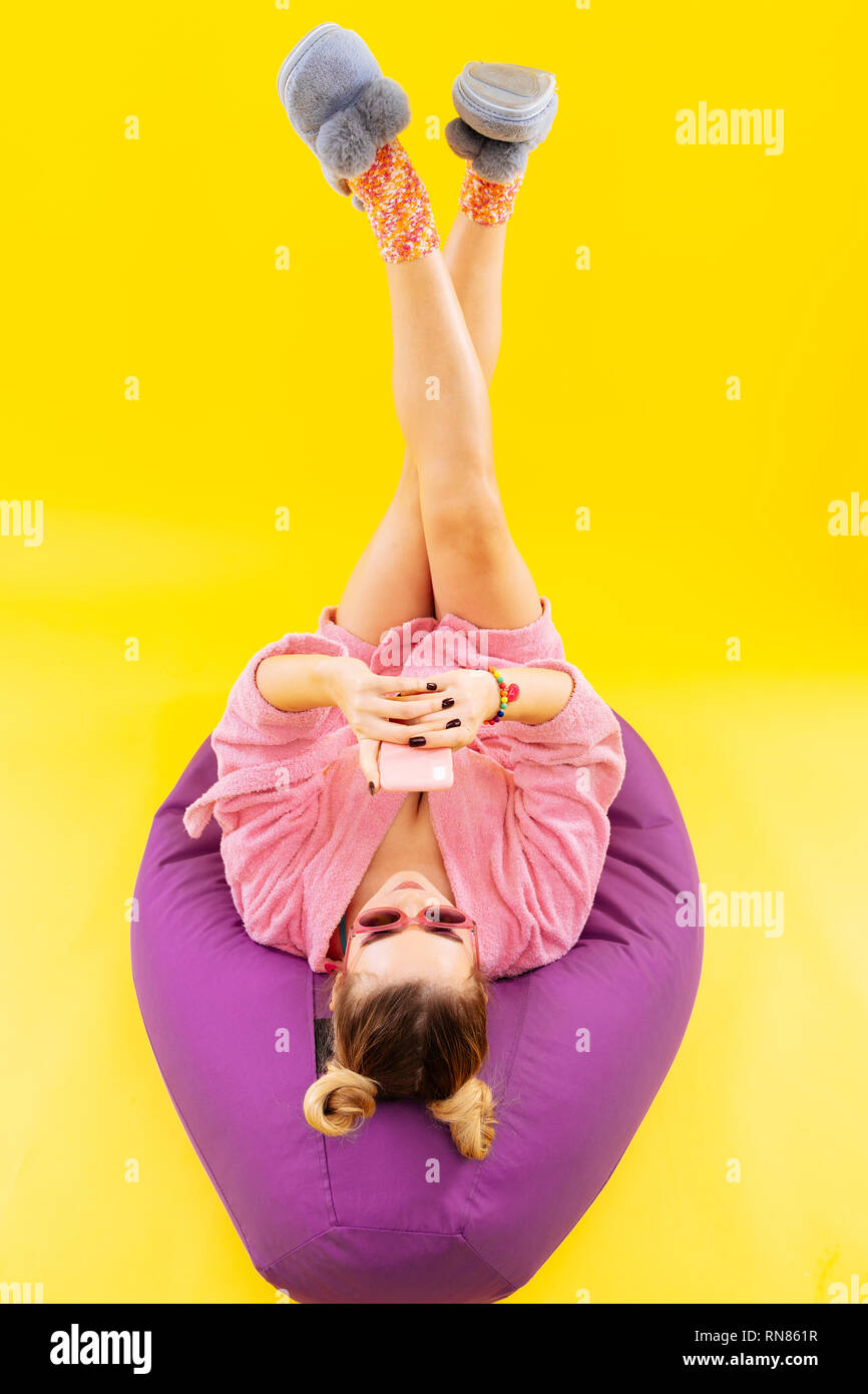 Young woman wearing fluffy house shoes chilling on beanbag chair - Stock Image