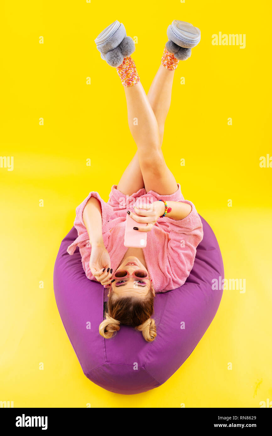 Woman lying on beanbag chair reading message from boyfriend - Stock Image