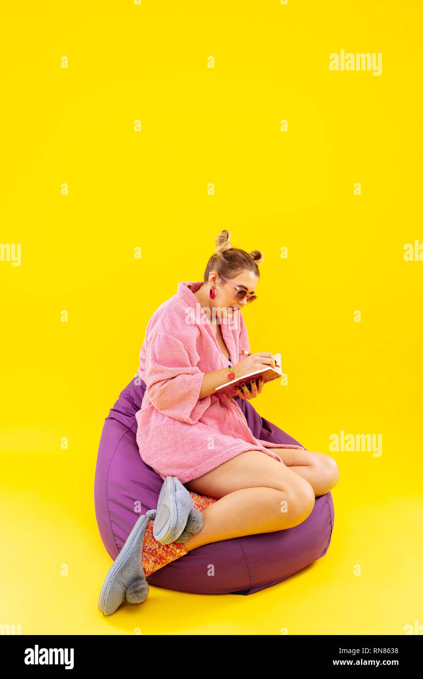 Blonde-haired woman sitting on beanbag writing in notebook - Stock Image