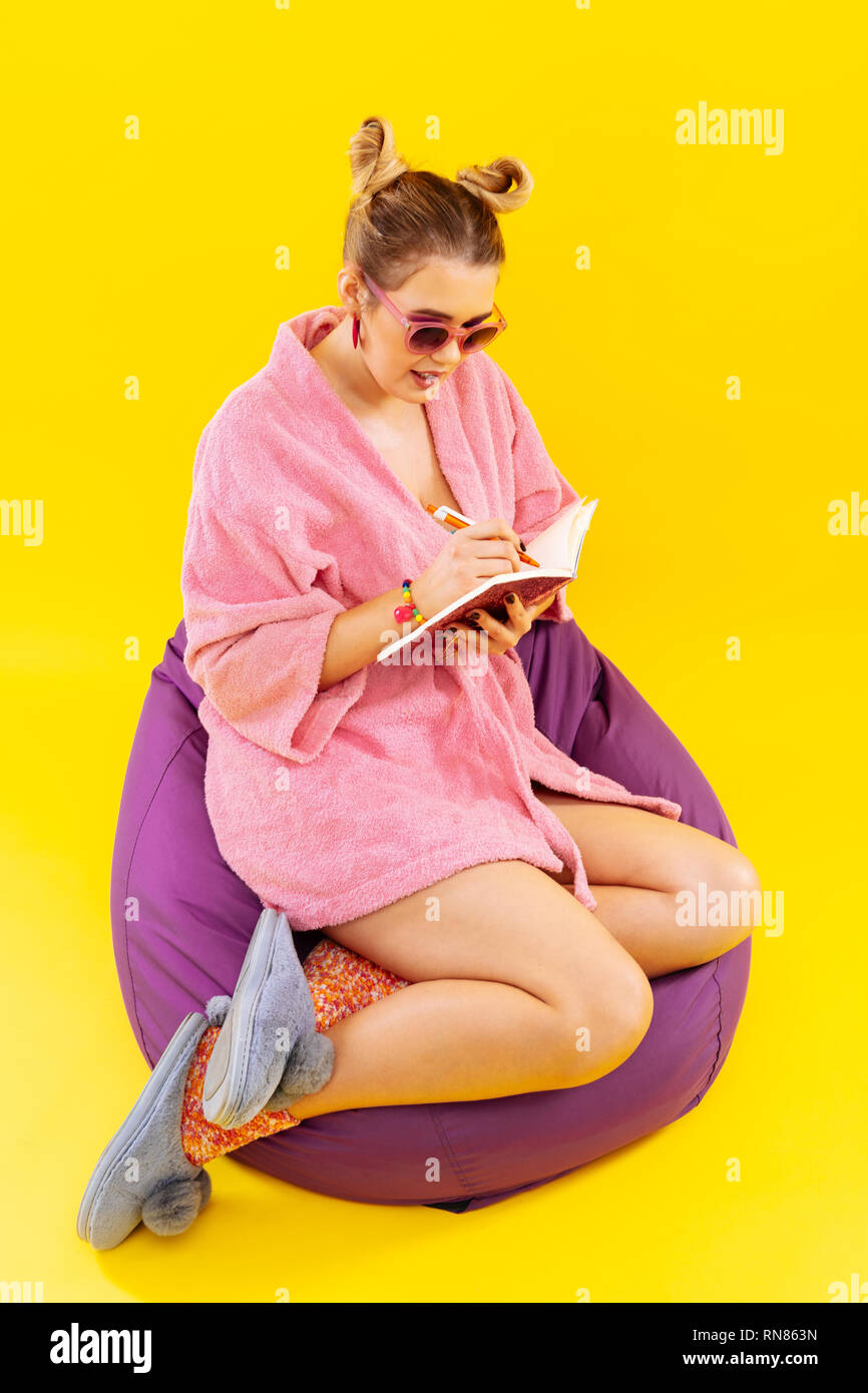 Blonde-haired woman wearing bathrobe writing in diary - Stock Image