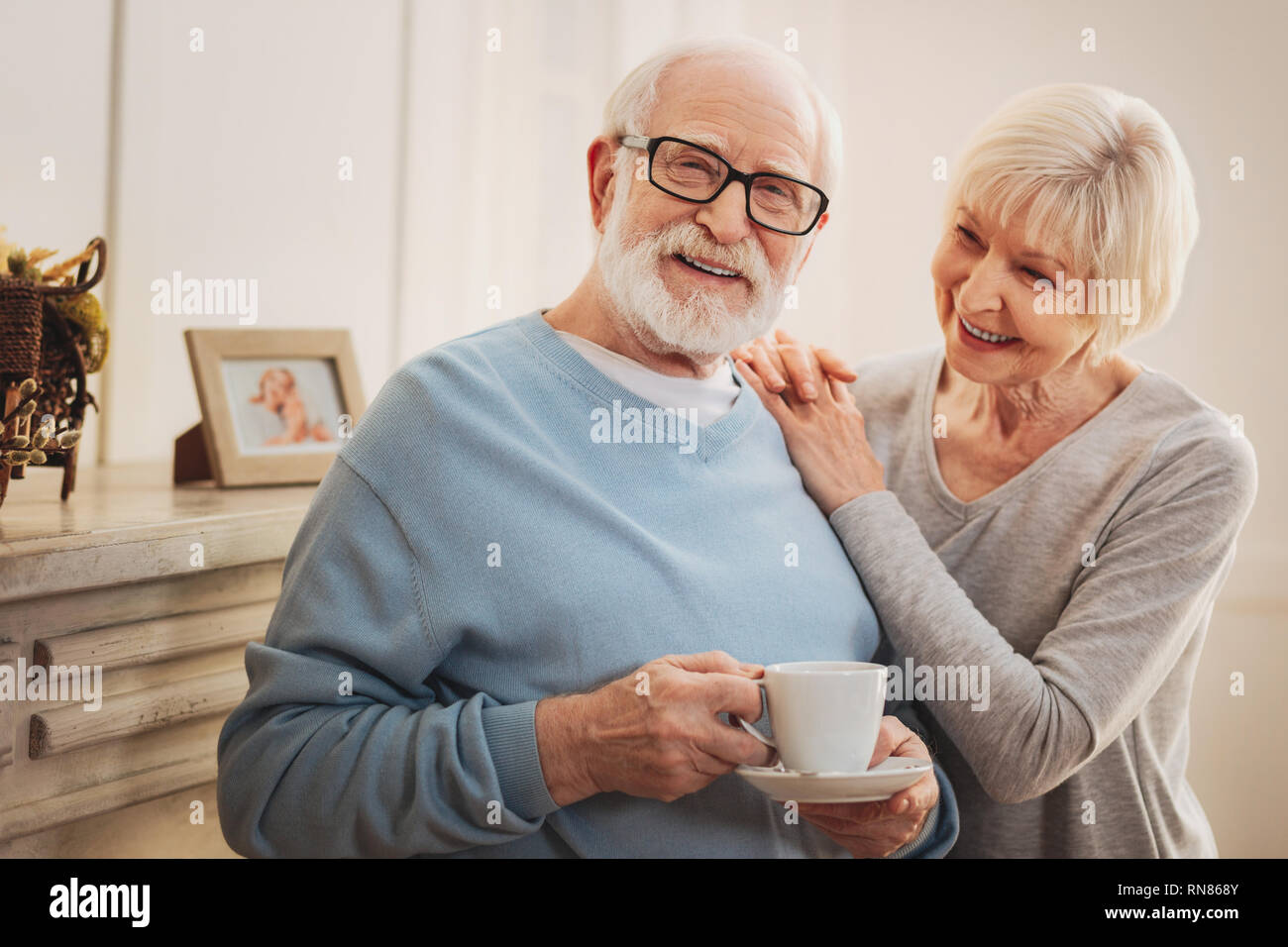Observant wife. Observant careful wife feeling respected while bringing some hot tea for her loving smiling man - Stock Image