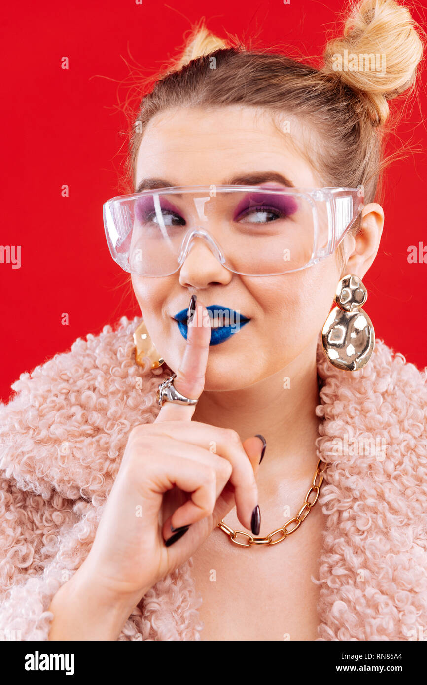 Fashionable woman with blue lips wearing stylish earrings - Stock Image