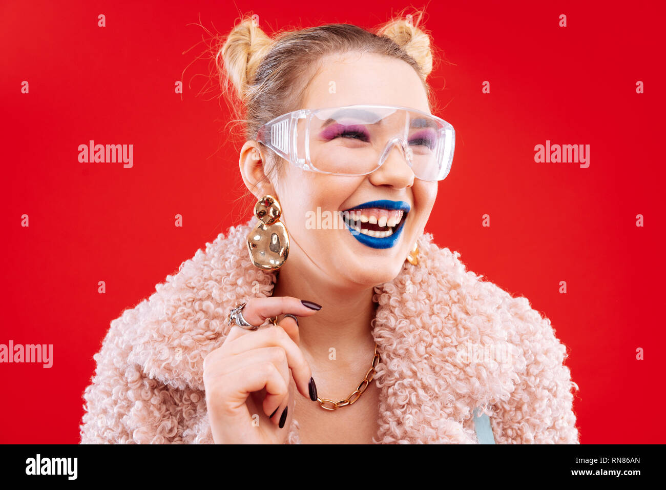 Cheerful woman with blue lips and pink eye shades laughing - Stock Image
