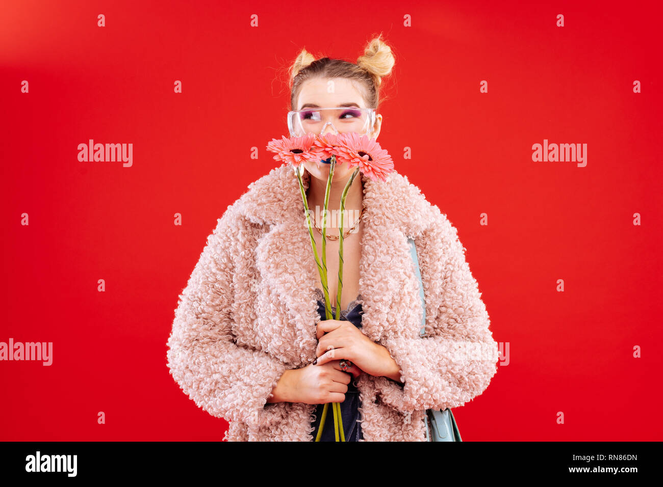 Fashionable blonde woman holding three beautiful flowers - Stock Image