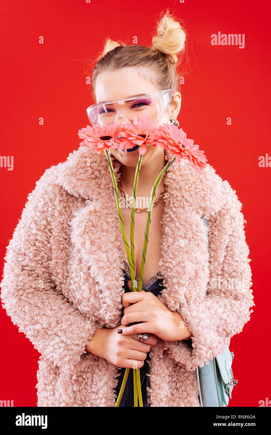 Young cheerful woman with pink eye shades holding flowers - Stock Image