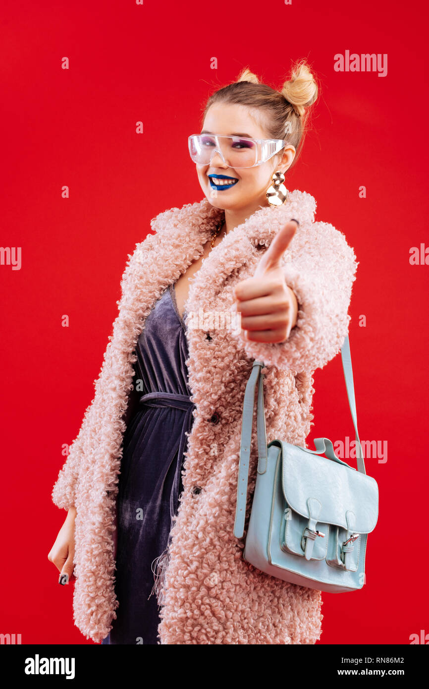 Fashionable woman wearing pink fluffy coat and blue bag - Stock Image
