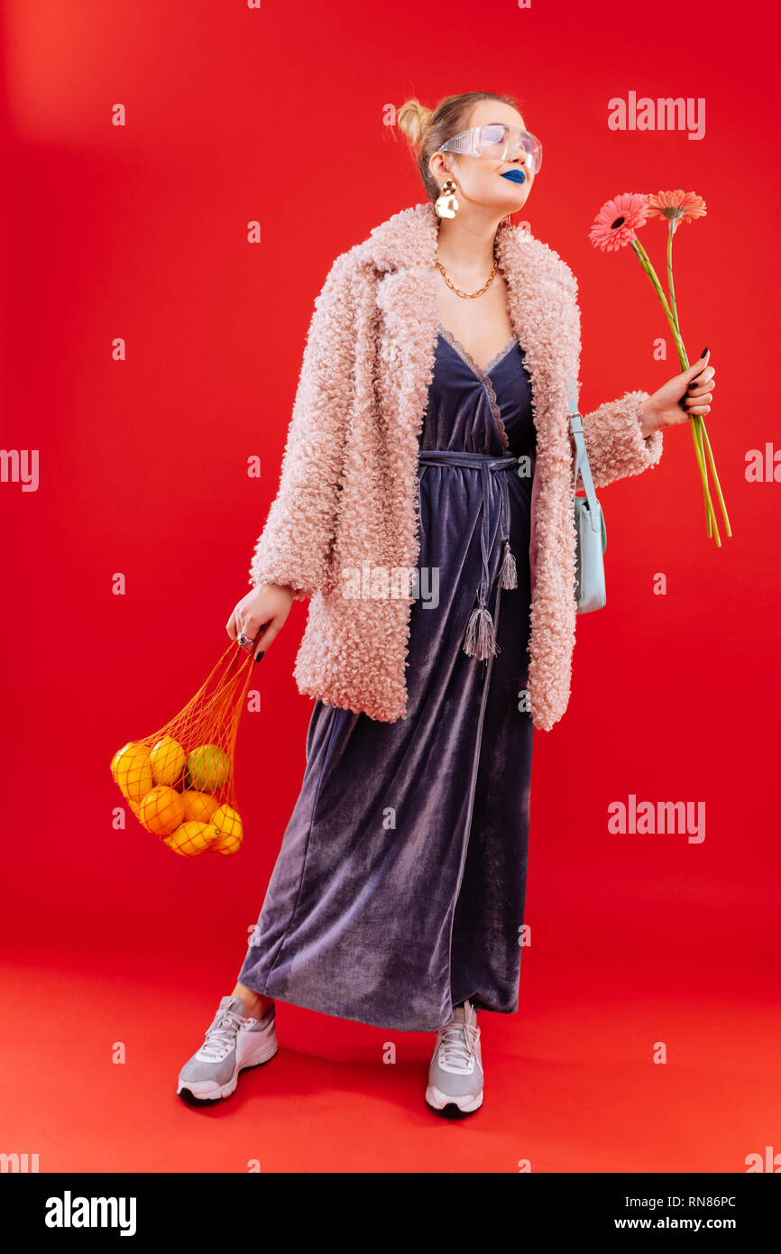 Fashionable woman coming home with bag of fruits and flowers - Stock Image