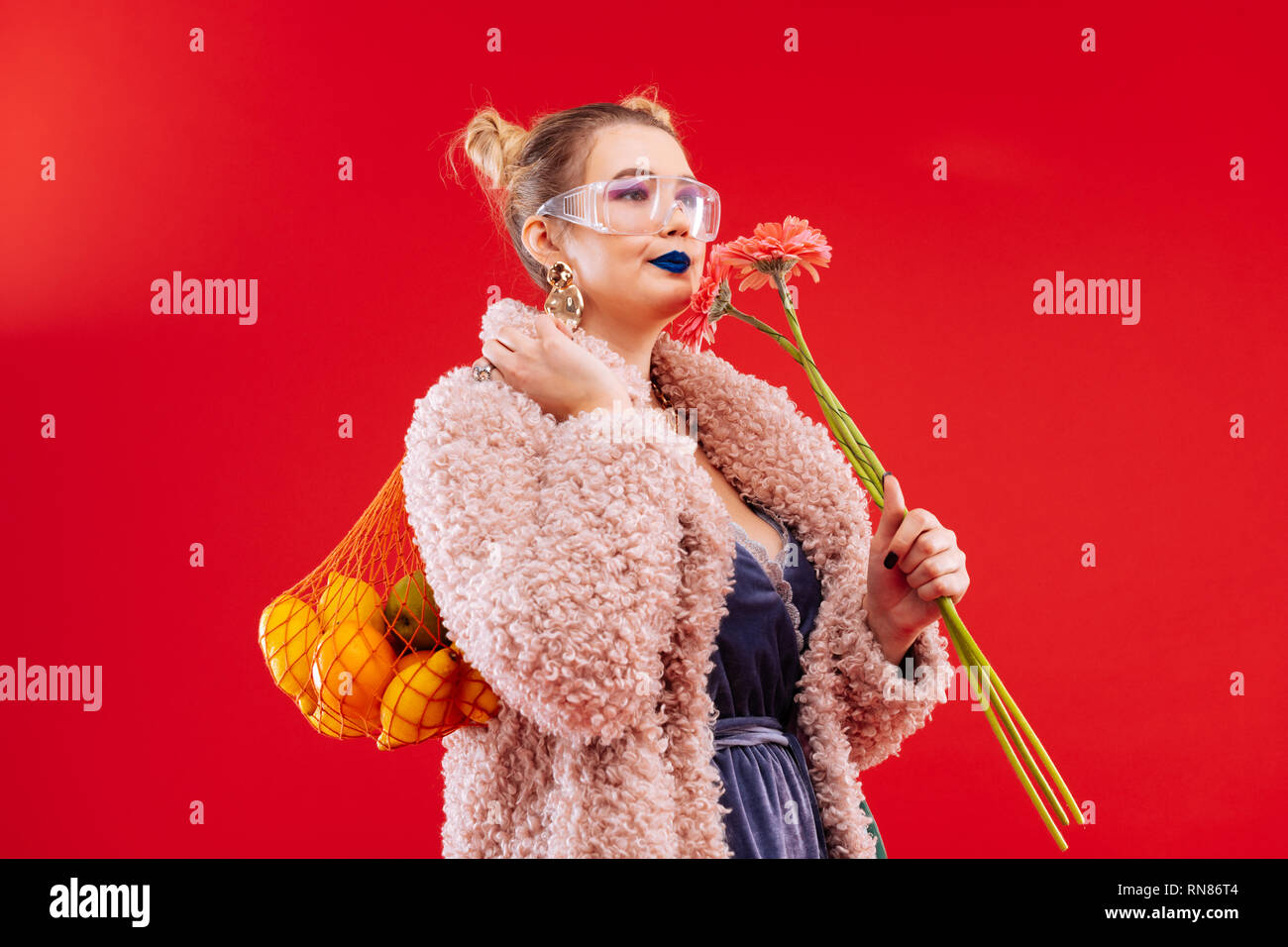 Woman with blue lips caring bag of fruits and pink flowers - Stock Image