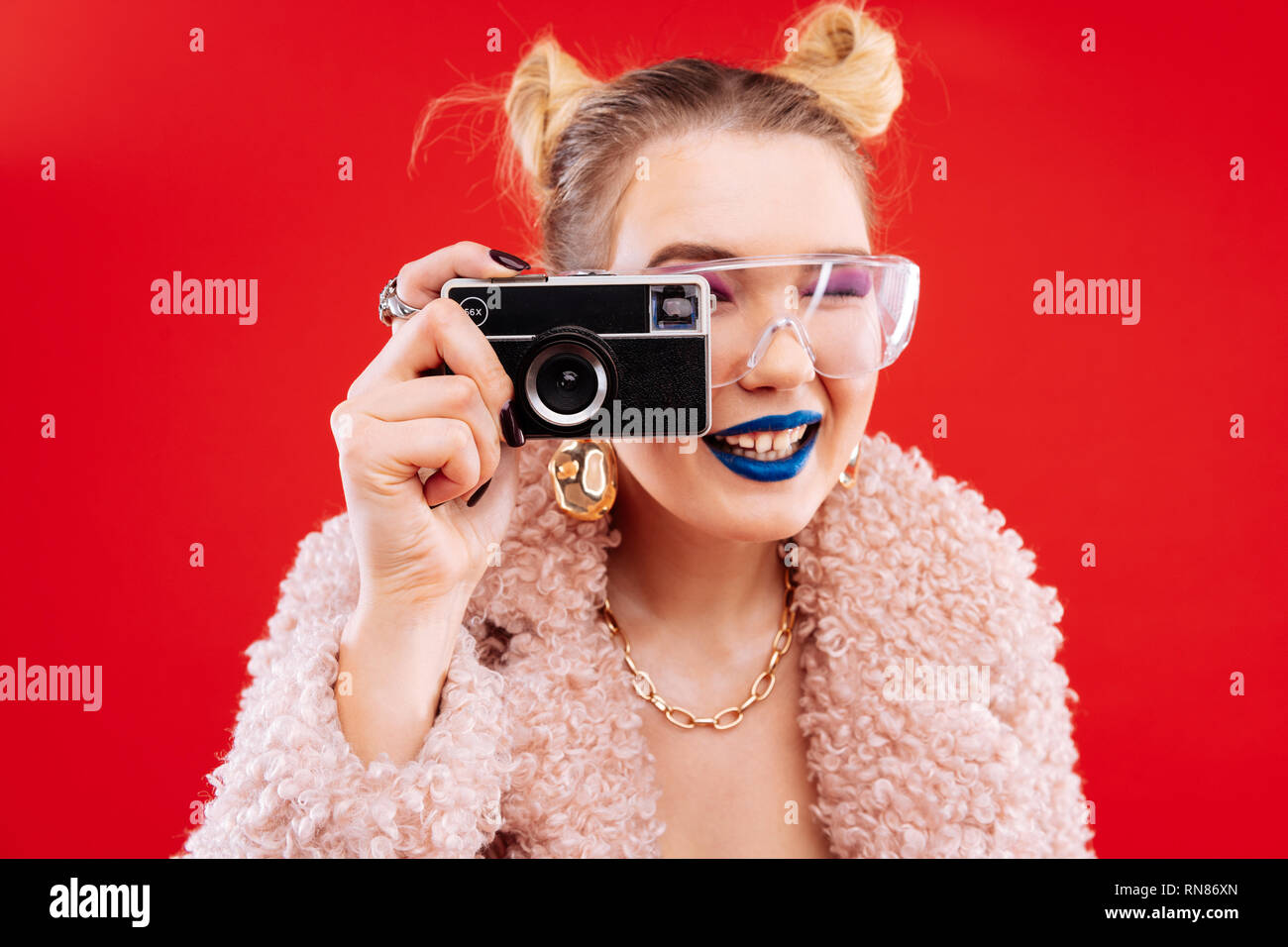Woman with blue lips and pink eye shades using camera - Stock Image