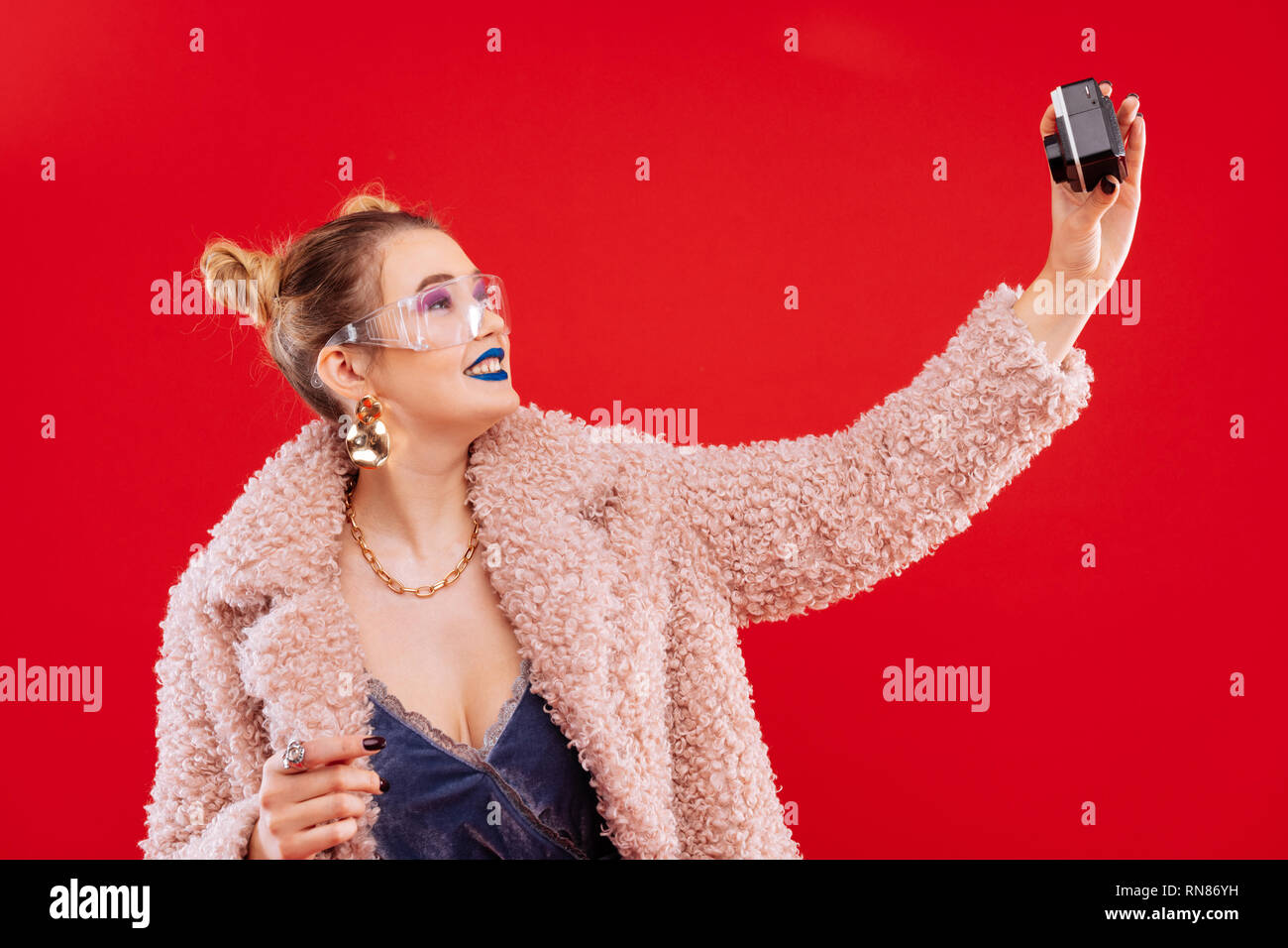 Fashionable woman with blue lips making selfie using camera - Stock Image