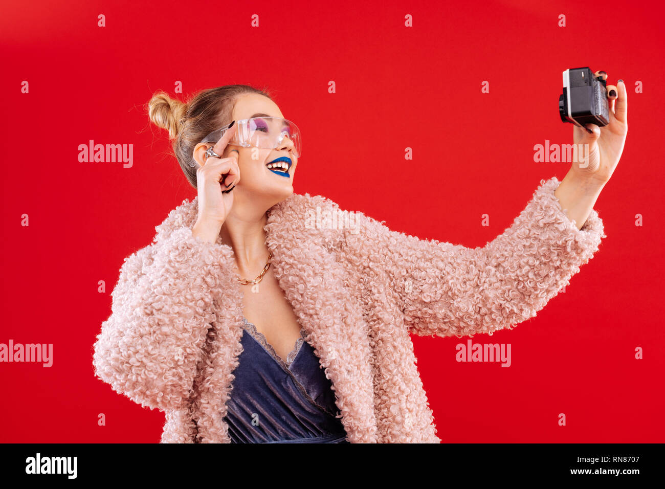Woman wearing pink fluffy coat smiling while making selfie - Stock Image