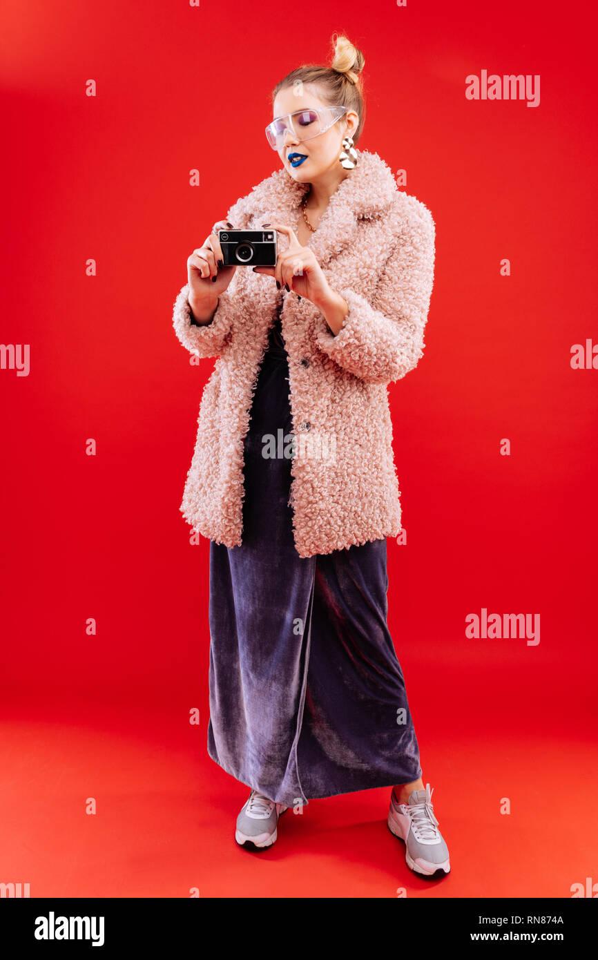 Slim woman wearing dress and pink coat holding photo camera - Stock Image