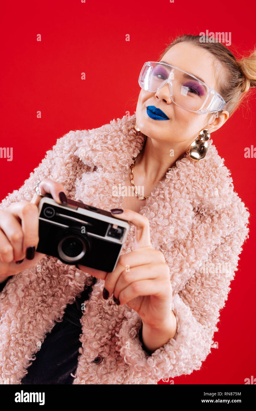 Woman with pink eye shades feeling excited before taking photos - Stock Image