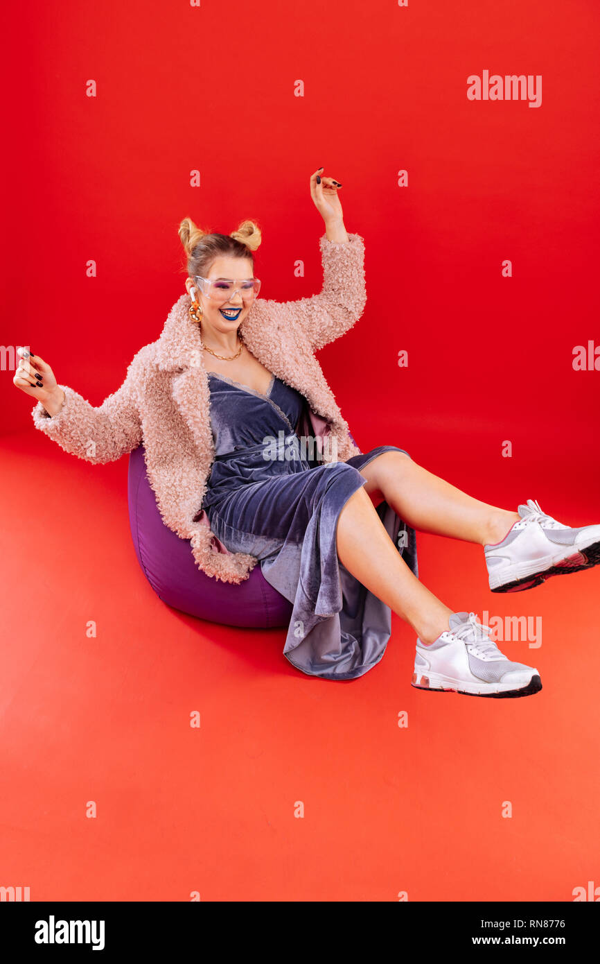 Fashion blogger wearing stylish sneakers sitting on beanbag chair - Stock Image