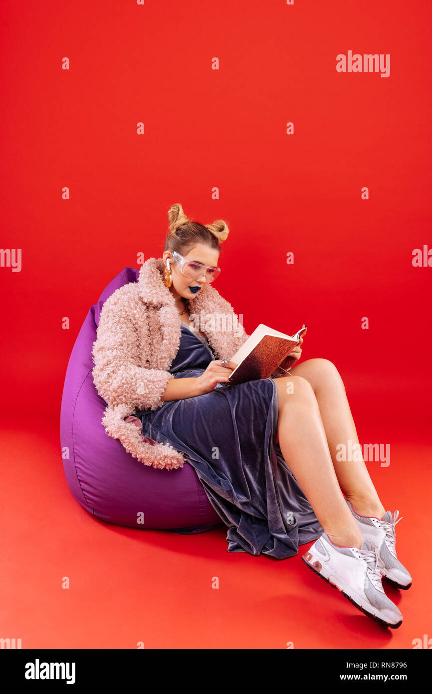 Woman with bright lips sitting in beanbag chair and reading book - Stock Image