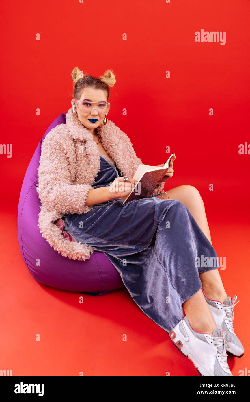 Woman wearing long dress and sneakers sitting in beanbag chair - Stock Image
