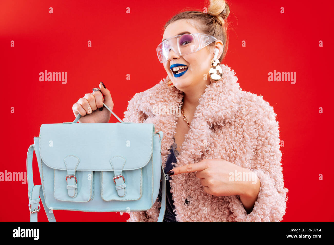Fashion blogger feeling satisfied getting her blue leather bag - Stock Image