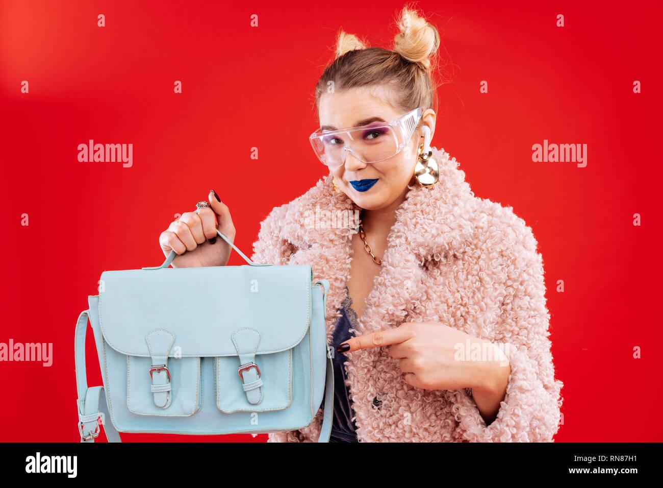 Shopaholic with makeup feeling amazing after buying new bag - Stock Image