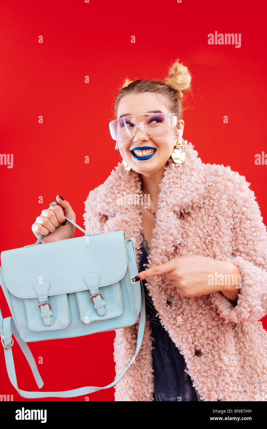 Blonde woman with blue lips smiling broadly after shopping - Stock Image